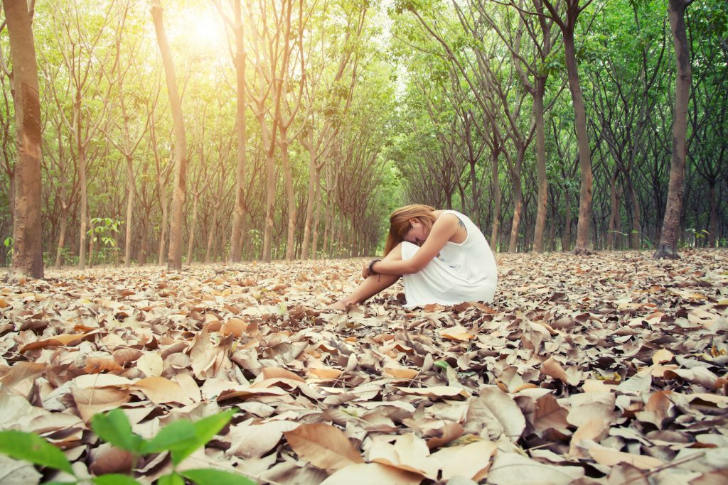Young asian woman sadly sitting on dry leaf in the forest alone